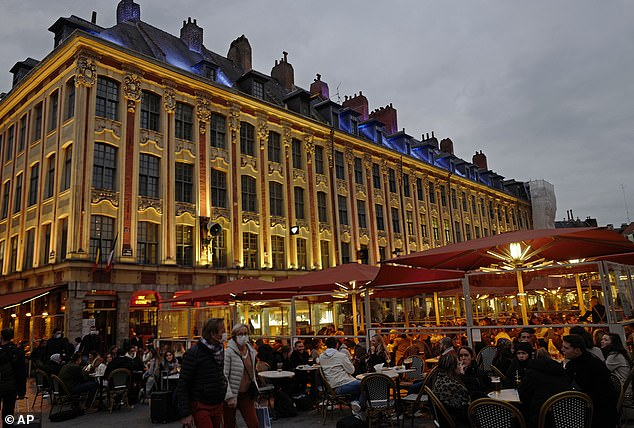 People enjoy a drink on a restaurant terrace in Lille, northern France before the city curfew