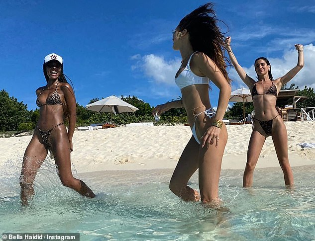Having fun: She splashed around in the water with friends, as she sported a white bikini