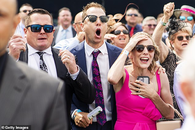 Trainer Matthew Dale (pictured centre) and wife Amy Dale (right) react during the running of race 5, the Kosciuszko