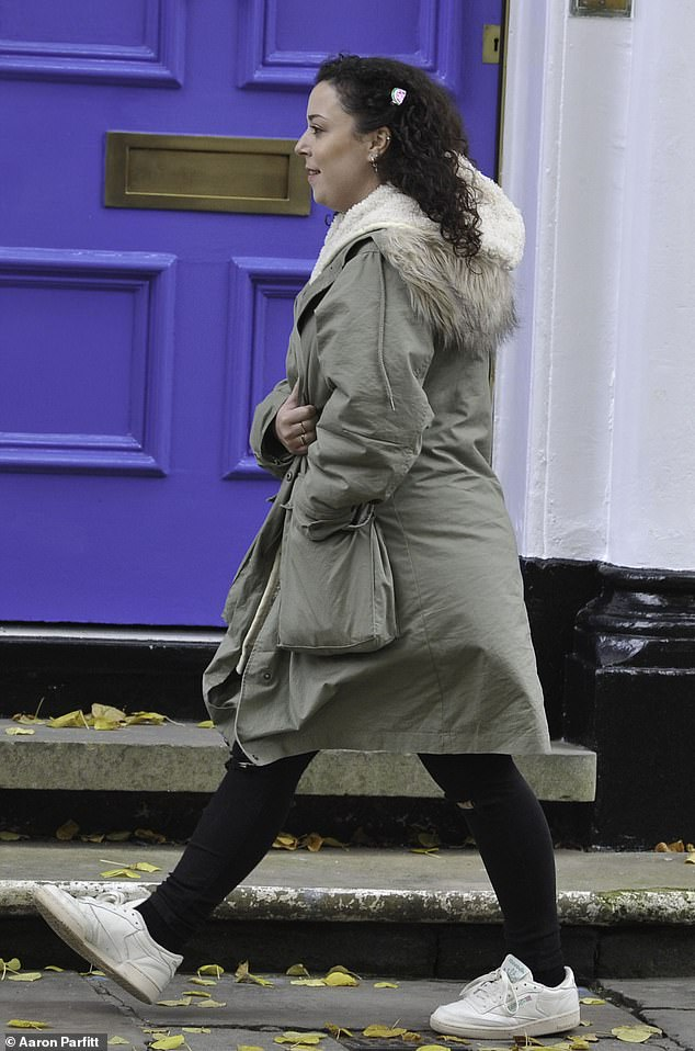 Cosy: Dani appeared in good spirits as she walked around in the large coat which had a furry hood and enormous pockets, teaming it with ripped black skinny jeans and white trainers