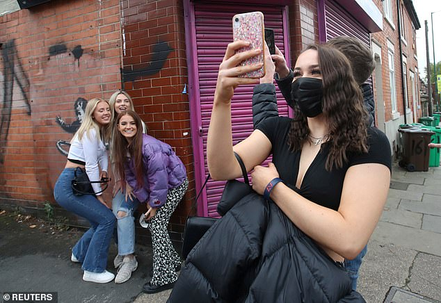 Lots of people have been coming to visit the mural. Pictured: Young people pose for photos in front of the new Banksy artwork