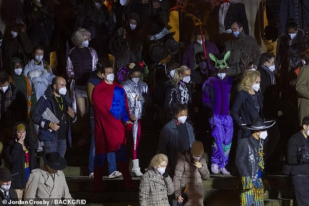 Standing out: The large group of extras donned an array of superhero costumes - and protective face masks - as they recorded the scenes in the city