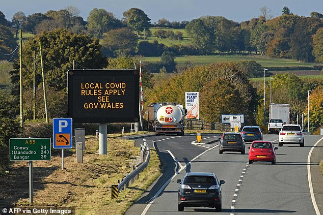 Traffic passes a 'local Covid rules apply' sign displayed along the A55 near Prestatyn in north Wales