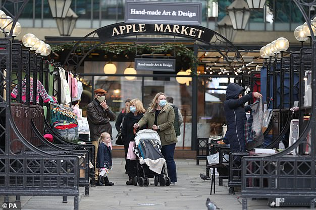 People wearing face masks pass by market stalls at Covent Garden in Central London on Thursday