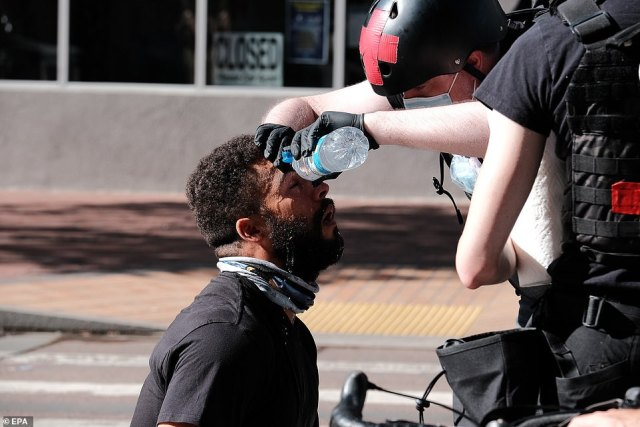 An activist's face is cleansed with water after the police deployed pepper spray as a crowd control tactic