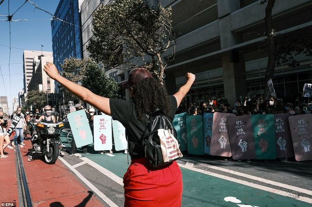 Opposing liberal activists march on Market Street with shields as protection from the San Francisco cops