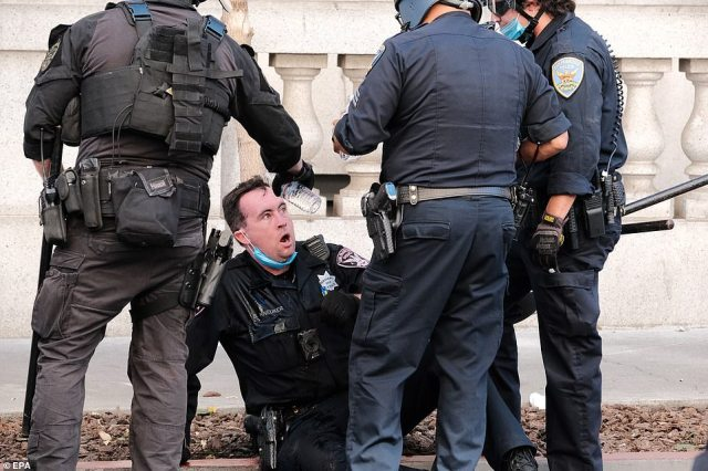 A San Francisco police officer's face is cleansed with bottles of water after an activist sprayed him with mace
