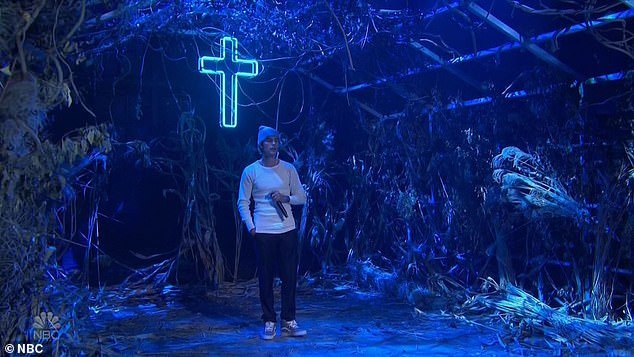 Dramatic setting: He wasin what looked like an overgrown, deconstructed greenhouse, dominated by a bright blue neon cross