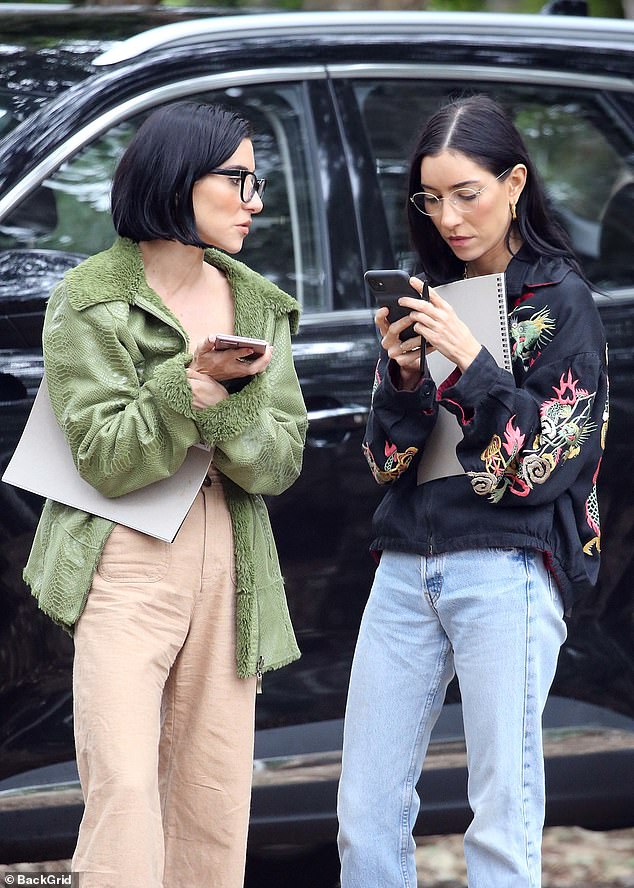 Hard at work:Dressed in trendy jackets, the twins, 35, looked concentrated as they walked along staring at their smart phones
