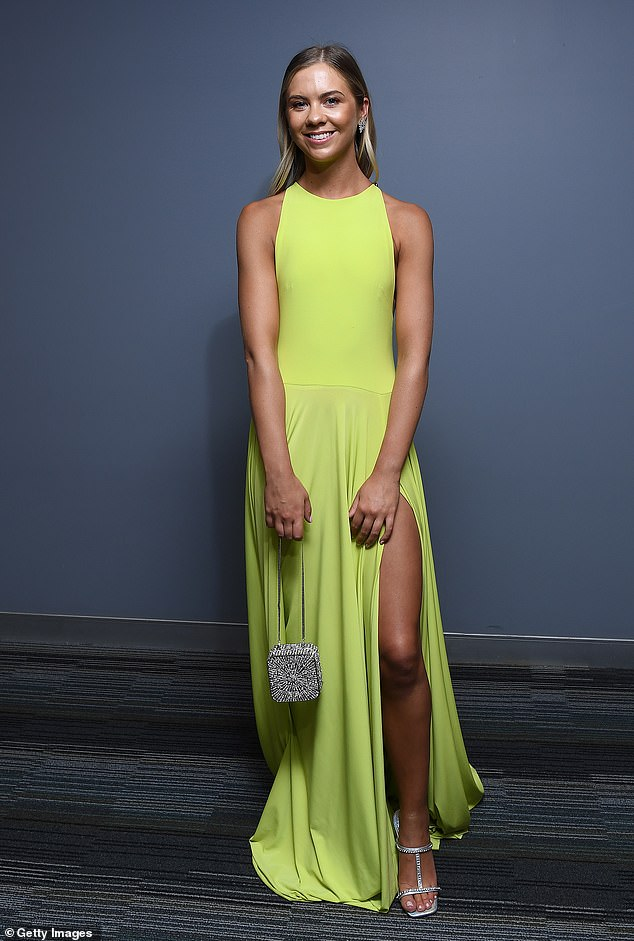 Classy:Ellie glowed in a sleeves yellow dress with flared skit and thigh-high split, while carrying a beaded handbag, along with silver heels