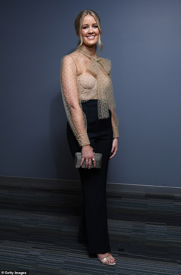 Simply chic:Emily wore a sheer blouse with dot detailing and a pussy bow at the neckline, to which she added high-wasited pants