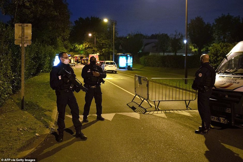 French police officers were seen standing guard and holding firearms at the end of the street where earlier a teenager suspected of beheading a middle school history teacher was shot dead after refusing to surrender