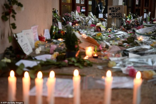 A photo shows flowers, candles and a placard reading 'I am a teacher, I am Samuel' at the entrance of a middle school in Conflans-Sainte-Honorine near Paris