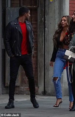 Laid back: Sean also opted for a casual look, wearing a bright red T-shirt with black jeans and a matching leather jacket