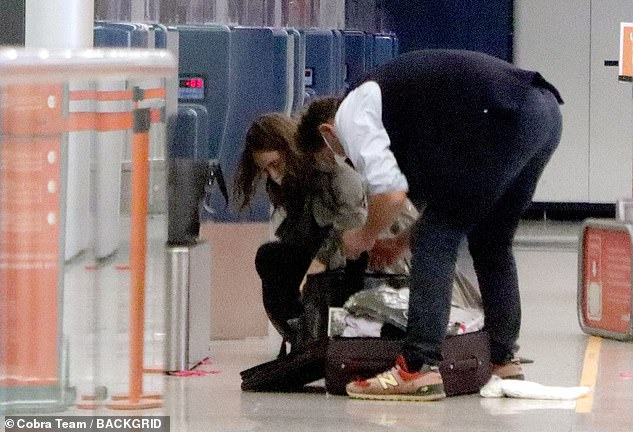 Bags: At one point, they were seen rearranging the contents of their bags while checking in