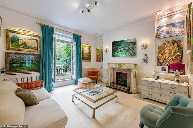 Old furniture, quirky decor and vintage wooden floors are present in nearly every room of Ronnie's home. Pictured: a living room with a grand fireplace and plush velvet curtains
