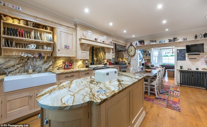 His kitchen offers a more sophisticated air, with polished marble countertops, wooden paneling and his signature shabby chic furniture