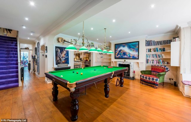 His downstairs snooker room features several music awards and electric guitars on display, along with his signature eccentric artworks