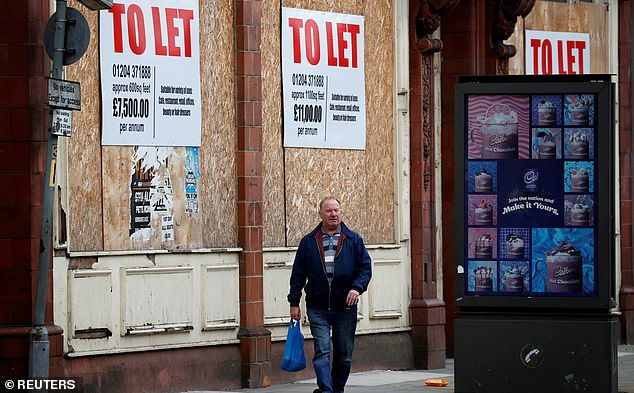 A record number of UK shops closed (pictured: A man walks by boarded-up shops in Bolton - library image) during the first half of 2020 due to the coronavirus lockdown, new figures have revealed