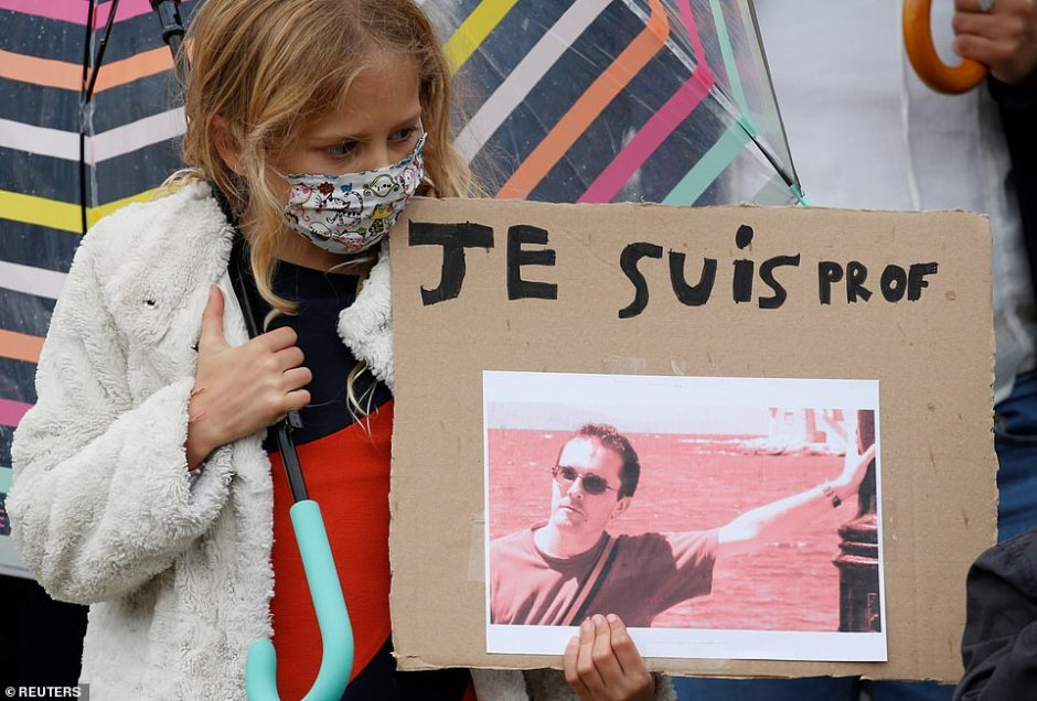 A young girl holds a banner with a picture of Mr Paty with a caption reading 'I am a teacher' as protesters showed their solidarity
