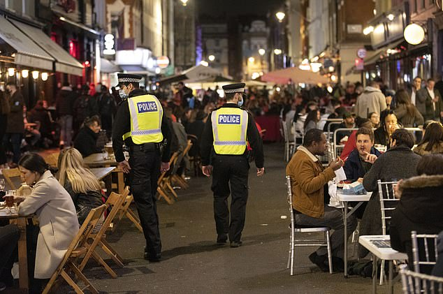 Police officers patrol the streets of Soho on Saturday night after London went into its first day of Tier 2 lockdown