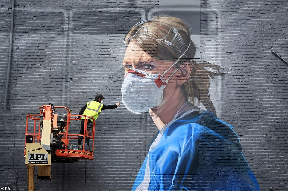 Artist Peter Barber works on a mural in Manchester city centre yesterday, depicting nurse Melanie Senior after The National Portrait Gallery commissioned the mural based on a photograph by Johannah Churchill