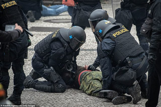 A protester is pinned to the ground by police officers. The growth in cases, with almost 100,000 this month in a country of 10.7 million, and 1,352 deaths overall from COVID-19, is forcing authorities to make plans for field hospitals and seek foreign help