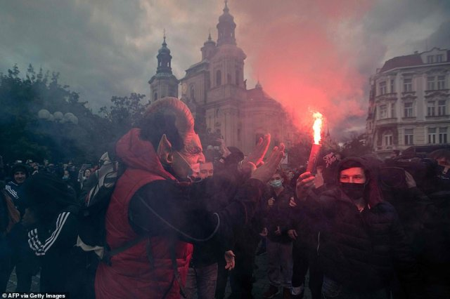Protestors light flares at the Old Town Square as hundreds of demonstrators, including football supporters, protest against the Czech government's new measures to slow the spread of the Covid-19 coronavirus in Prague on October 18