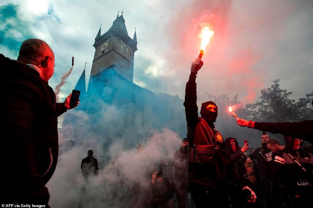 Protestors light flares at the Old Town Square as hundreds of demonstrators, including football supporters, protest against the Czech government's new measures to slow the spread of coronavirus in Prague on October 18
