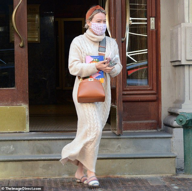 Earth tones: She wore a burnt sienna headband, striped slippers and gold hoop earrings, while carrying a copy of Brit Bennett's critically acclaimed bestseller The Vanish Half to read later