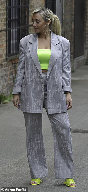 Work it: The actress brightened up her grey suit with splashes of neon colour in her crop top and heels