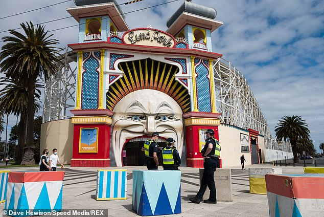 Police are seen in large numbers patrolling the grounds of Luna Park during COVID-19 in St Kilda on October 18