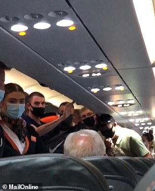 Flight attendants can be seen intervening
