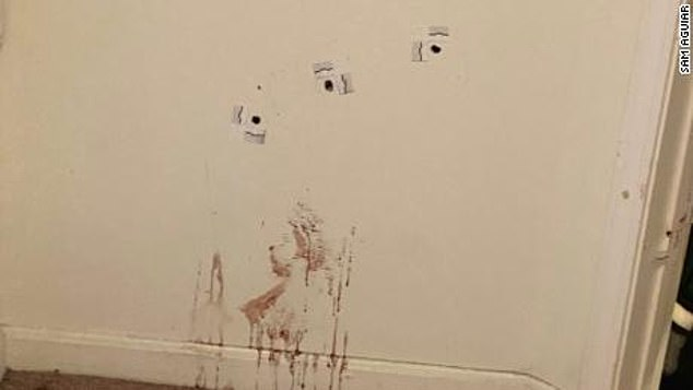 Gunshots and blood are seen on a wall inside Taylor's apartment after the deadly raid