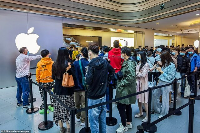 Customers pictured here queueing to get their reserved iPhone 12 smart phones at an Apple Store in Shanghai on Friday