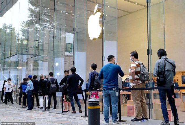 Outside an Apple Store in Tokyo, Japan this morning. To mark the launch, Deirdre O'Brien, Apple's senior vice president of Retail and People, made the claim there has 'never been a better time to get an iPhone', despite the economic crisis and global pandemic