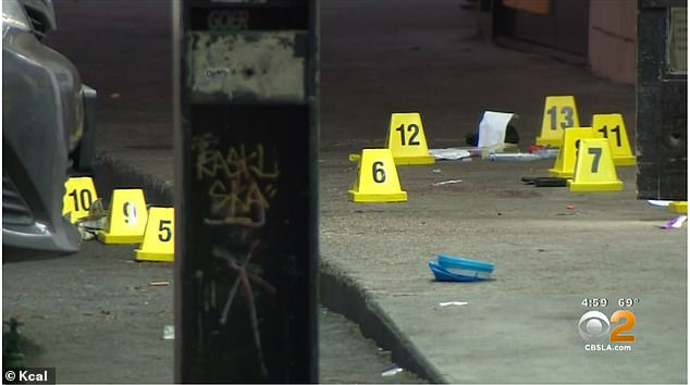 The scene of the shooting Friday morning after the allegedly armed black man was wrestled to the ground and shot four times at close range by a cop outside a liquor store