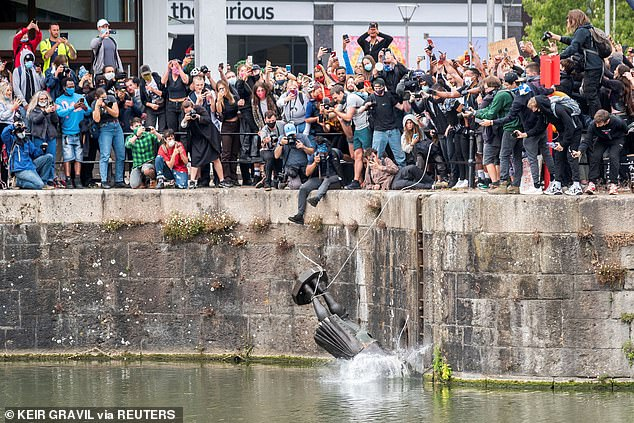 The statue of slave trader Edward Colston falls into the water after protesters pulled it down