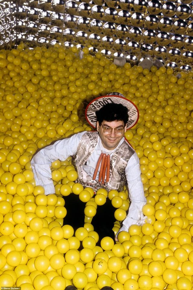 Ball pits: Michael Musto is seen at the John Wayne Bobbitt party that he hosted at the Tunnel in 1994. 'Musto wore an outfit fitting of he occasion made of tabloid newspapers and the piece de resistance hotdogs strung together as a necklace. To top it all off I put him in the 'ball room' for the photo op,' the photographer says