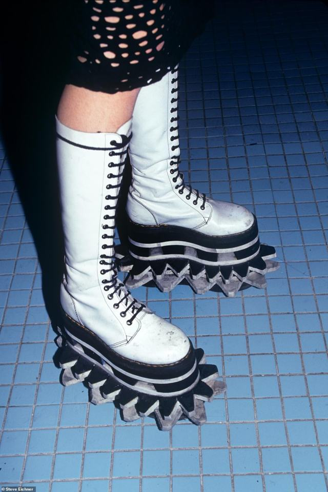 In style: Sky-high platform shoes were all the rage seen in this photo at the Limelight in 1993. 'Usually, homemade, and the taller the better,' the author writes. 'Start with a pair of doc martins or sneakers the glue together flat foam pieces stacked up in multi-colors. Cut the edges into jagged patterns and voila! The wearer of these shoes towered over the crowd. It was hilarious watching the club kids try and walk in these things. They had the strangest gait to avoid falling or kicking someone with the points. The funniest was watching them try to navigate a staircase'