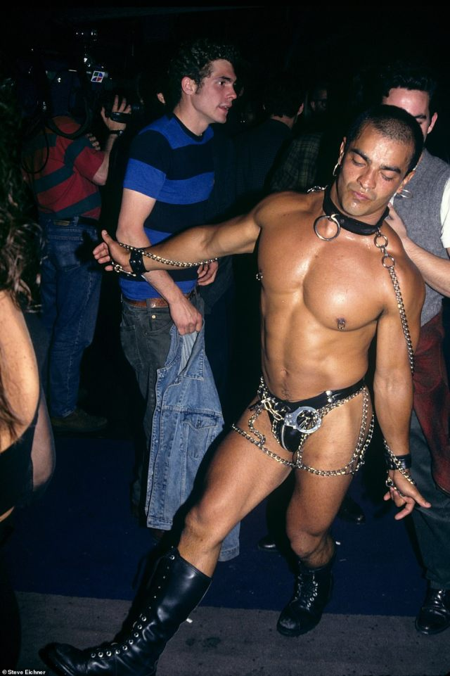 Leather and chains: A dancing clubgoer is seen at Club USA in 1993. 'This is one of my favorite photos in the book and kind of says it all about the 1990s club scene in NYC,' the photographer says. 'Anything goes! Here we see a very fit man dancing to the music in boots and a leather G-string and nothing else except his bondage accessories, handcuffs and a leash'