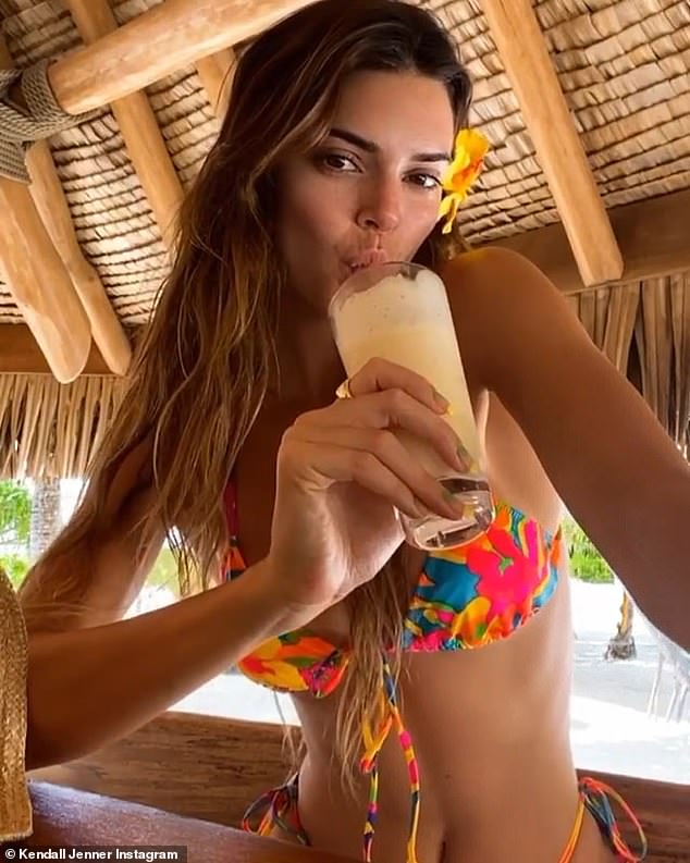 Beach babe: Kendall enjoyed a fruity drink as she relaxed in the shade
