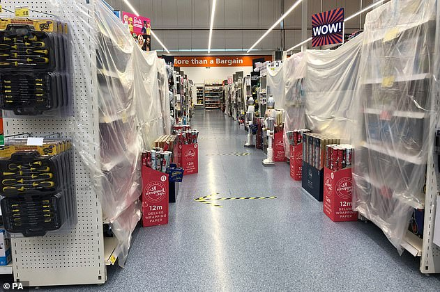 """Shopping aisles are surrounded by plastic sheeting at a Newport store as Wales enters first week of a week """"firewall"""" lockdown in an attempt to protect the country's NHS from being overwhelmed by the coronavirus resurgence"""