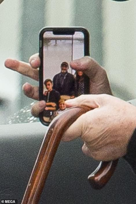 A tribute: Despite their troubles, the background on Phil's phone seemed to show a picture with Orianne and their sons