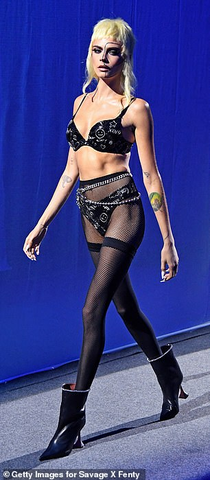 Cara Delevingne, 28, modeled a black velvet bra with silver embroidery and matching panties, which she combined with fishnet stockings and ankle boots with heels