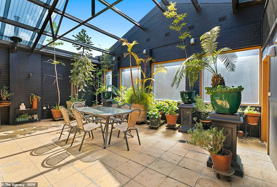 At the rear of the house is a four-car parking garage and a raised sunlit terrace (pictured), perfect for entertaining