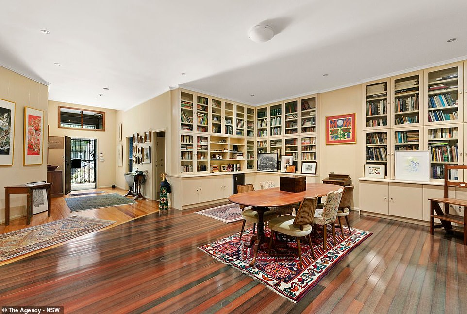 A library-inspired book case lines two walls in the downstairs living room