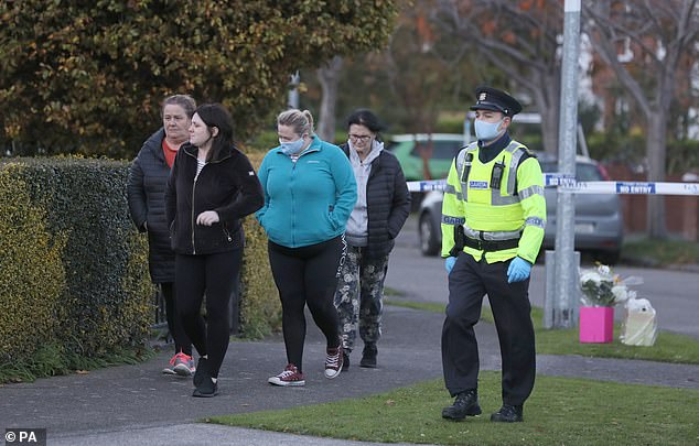 People leave after planting flowers near the scene at the Llewellyn estate in Ballinteer
