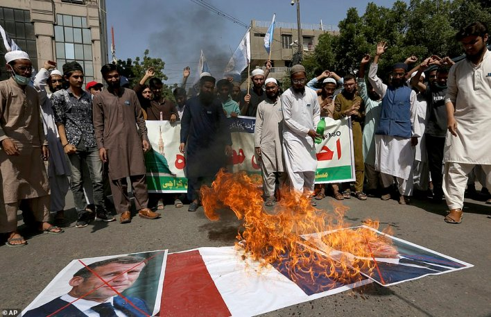 PAKISTAN: Protesters from the Muslim Students Association in Karachi burn a French flag next to defaced images of Emmanuel Macron during the latest demonstration against the French leader today