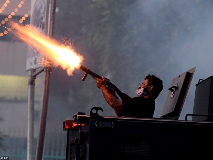 A police officer fires tear gas shell to disperse protesters marching to the French Embassyin Islamabad, Pakistan